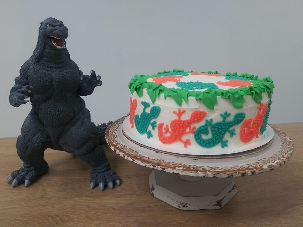 A multicolored cake with a dinosaur toy