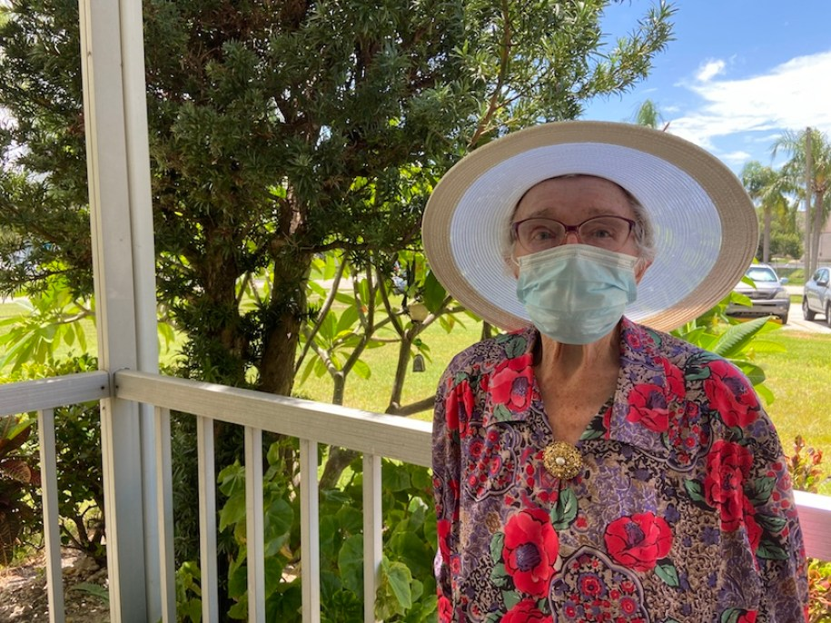 Barbara Rygiel in large hat, flowered shirt and face mask