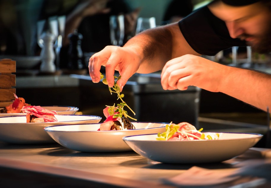 A chef adding garnish to two finished plates in the kitchen