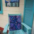 Gecko painting on a blue Adirondack chair on a porch with blue shutters.