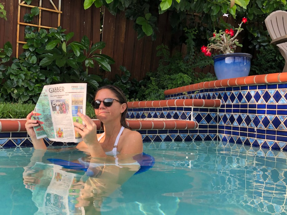 Woman with sunglasses reading the Gabber newspaper in a poll with blue tile