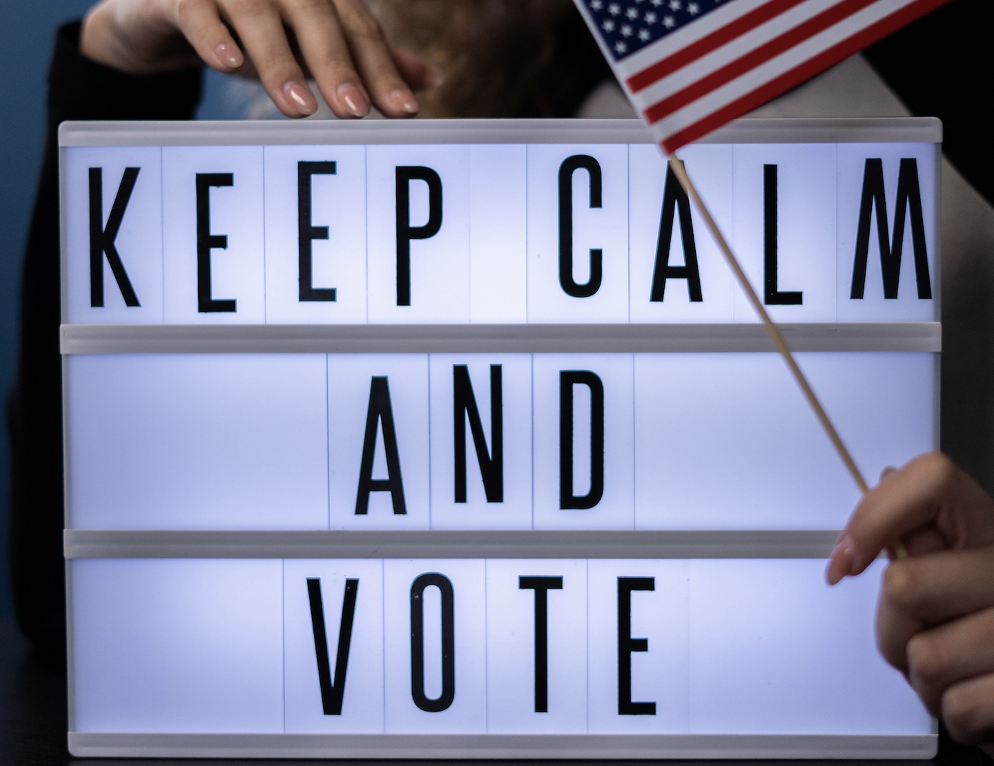 Picture of a sign that says Keep Calm and Vote with woman's hands holding small American Flag