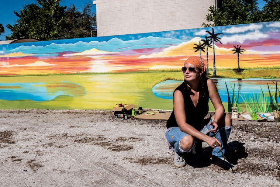 Kiersty Long works on a mural in Artist's Alley behind Sea Dog Cantina