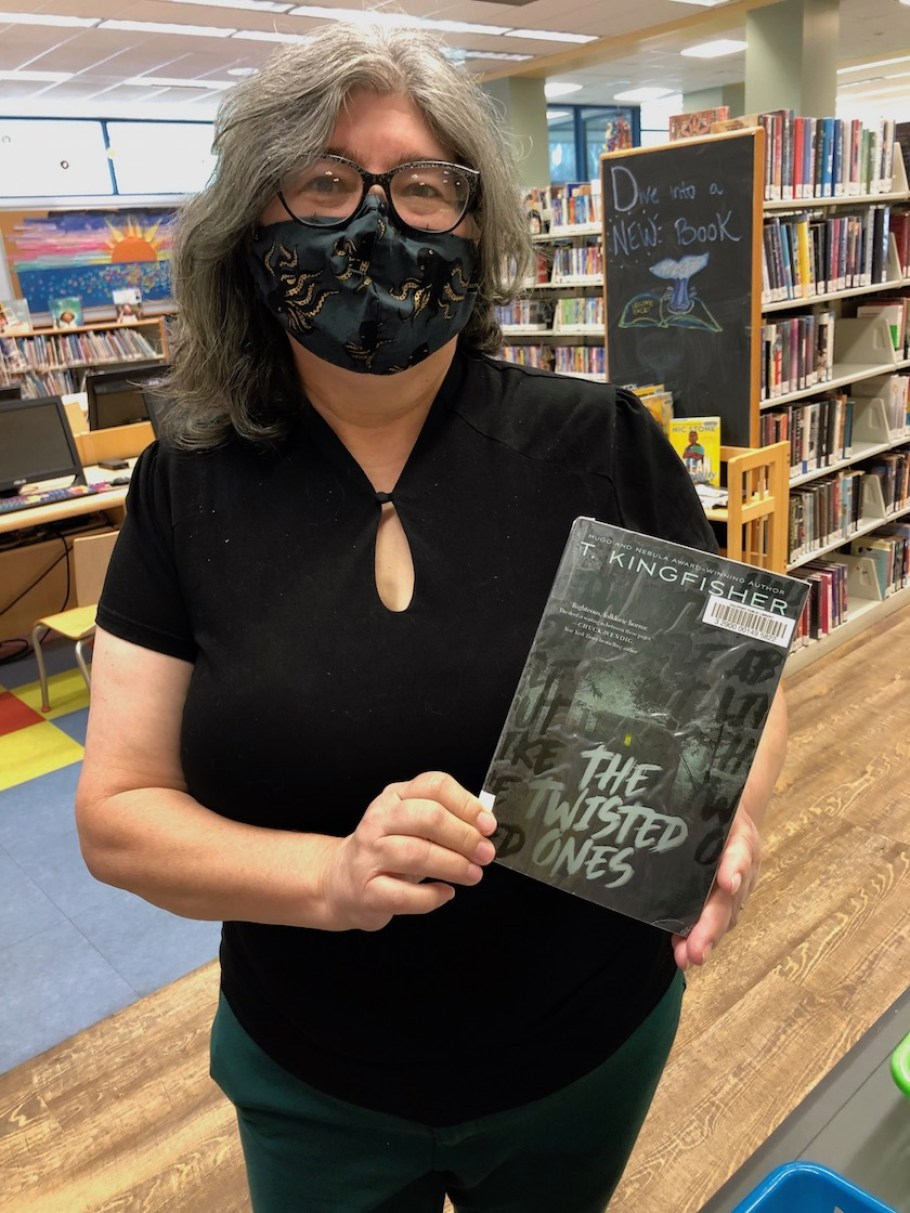 A woman in a face mask holding a book
