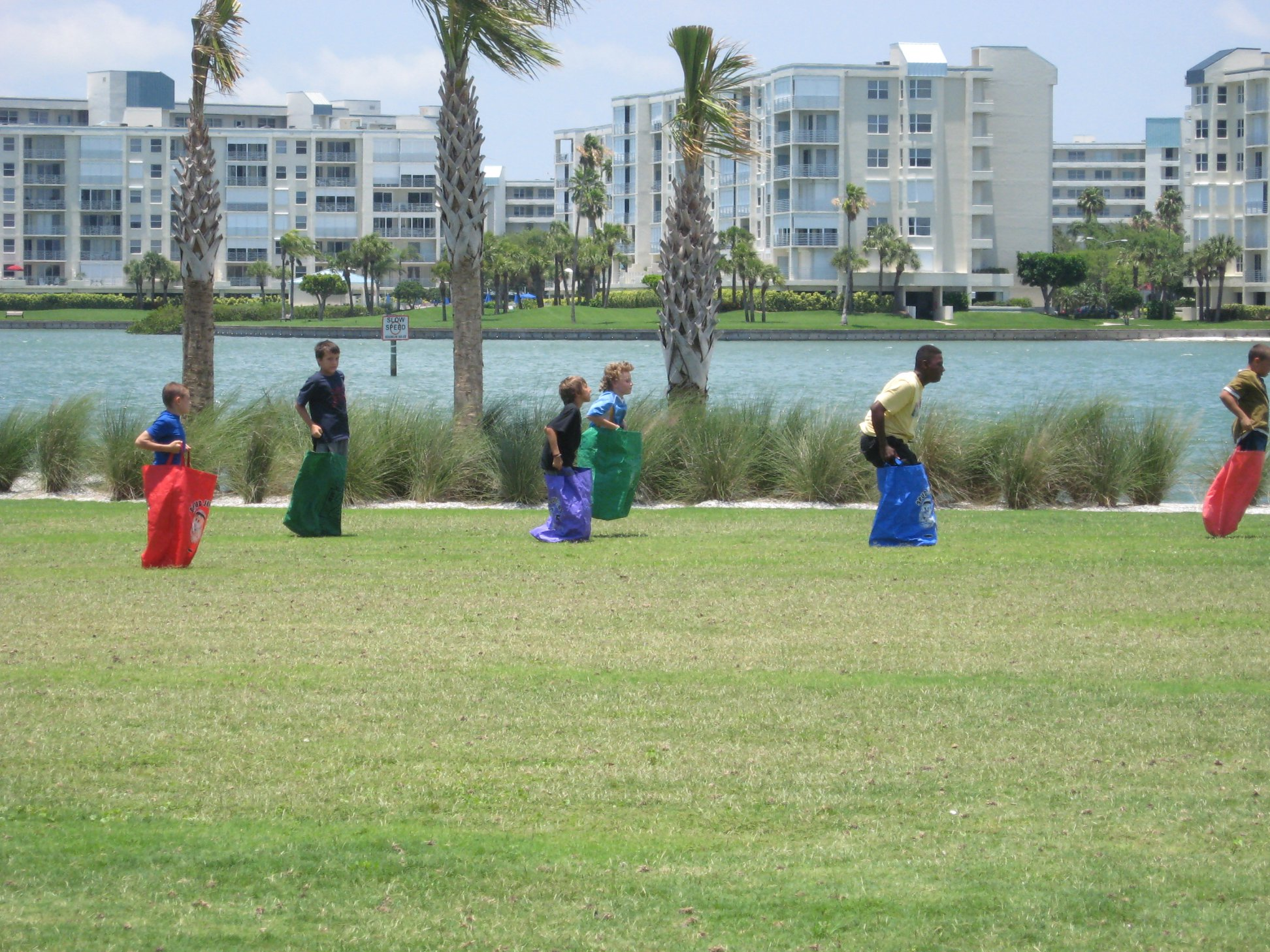 Kids in a sack race with water and buildings in the background