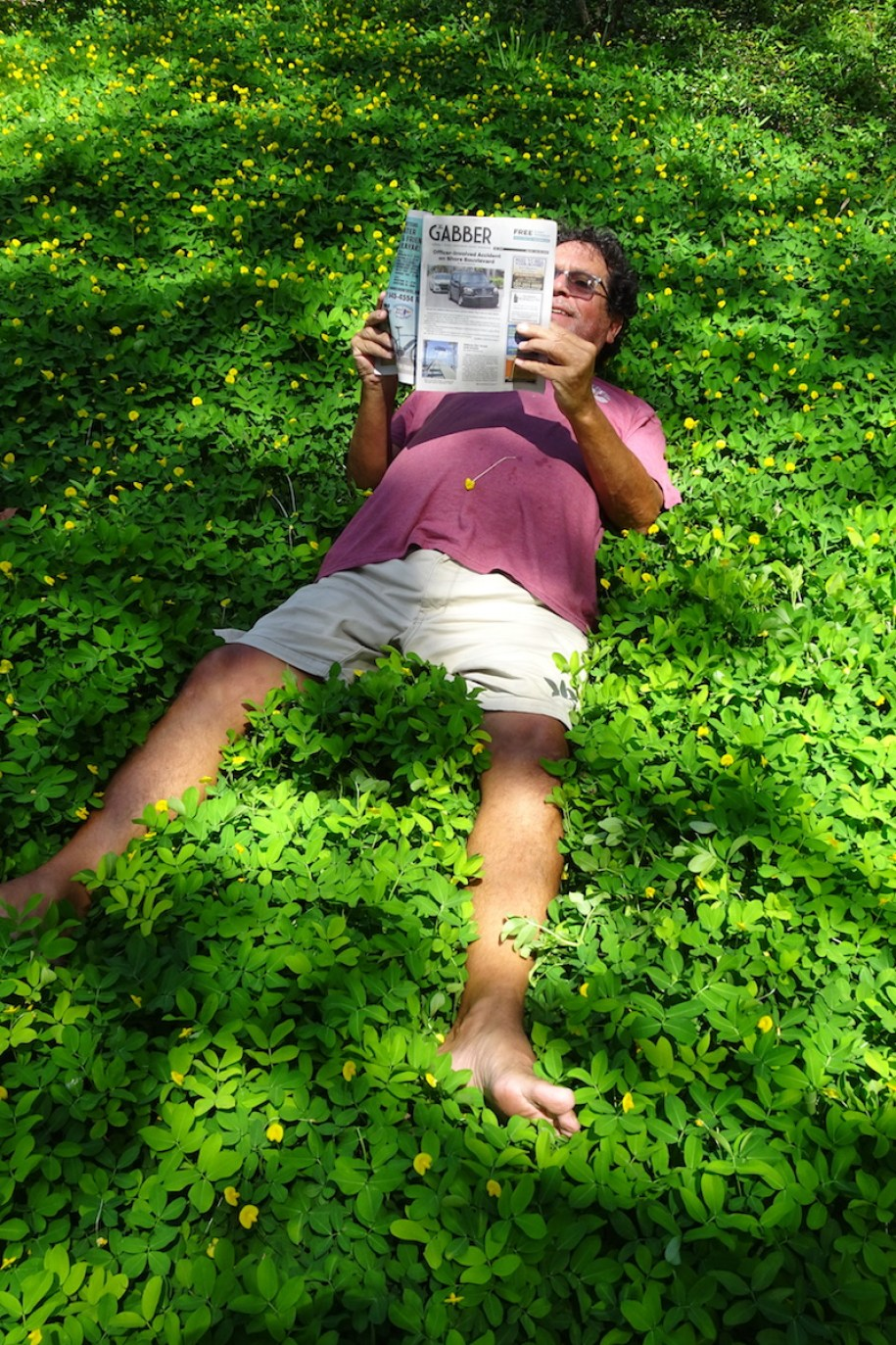 Man in shorts and t-shirt lying on the grass reading a Gabber Newspaper Gulfport Florida