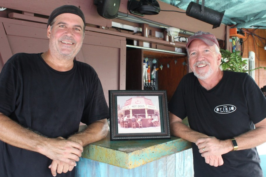 Two men in black shirts pose next to a vintage photo of a hot dog stand.