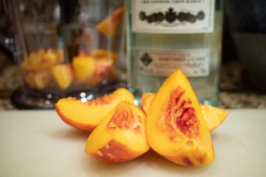 Cut peaches with rum bottle in background