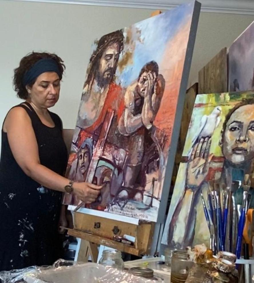 A woman painting art on an easel in her studio.