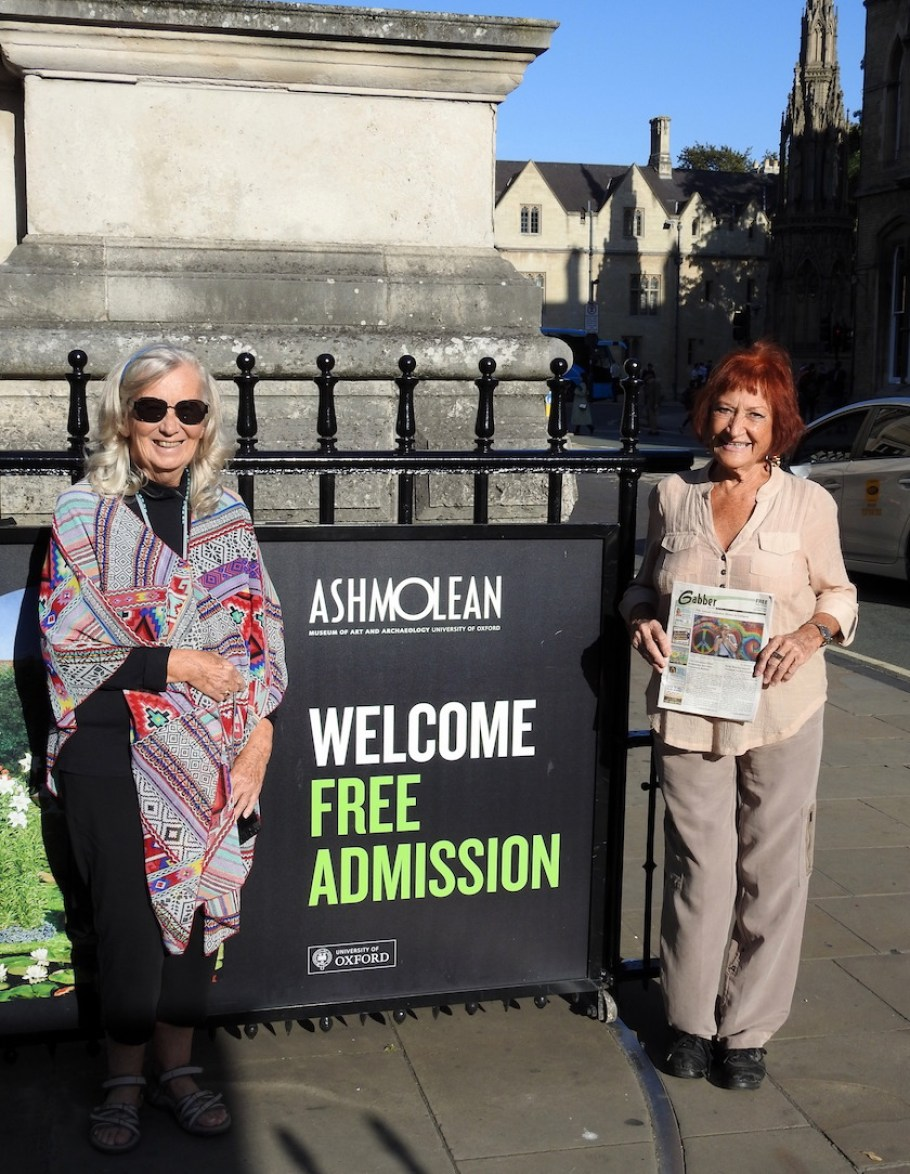 "Two women standing in front of a sign that reads ""Welcome Free Admission"" and holding a Gabber Newspaper"