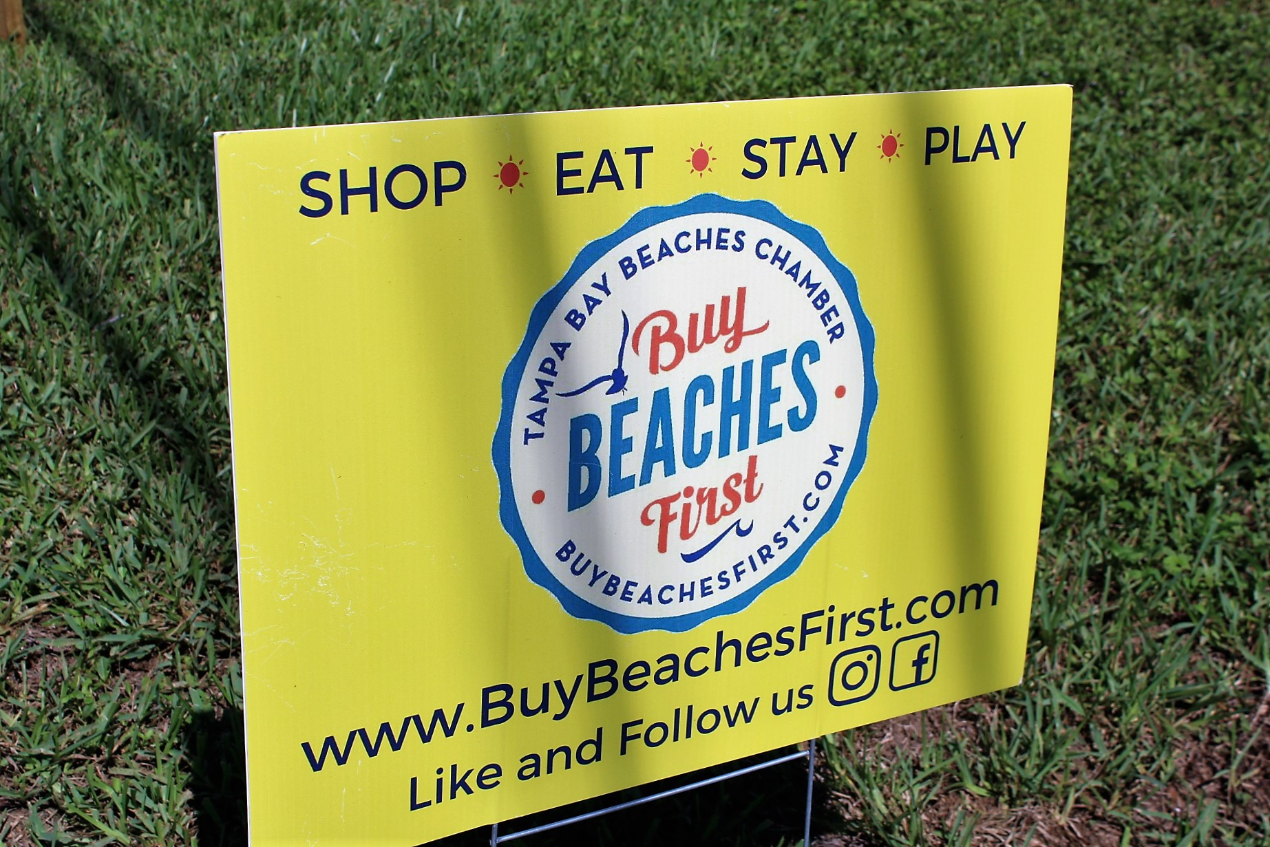 """A yellow sign in a yard that reads """"Shop, Eat, Stay, Play; Buy Beaches First; www.buybeachesfirst.com; Like and follow us on"""" Instagram and Facebook symbols."""