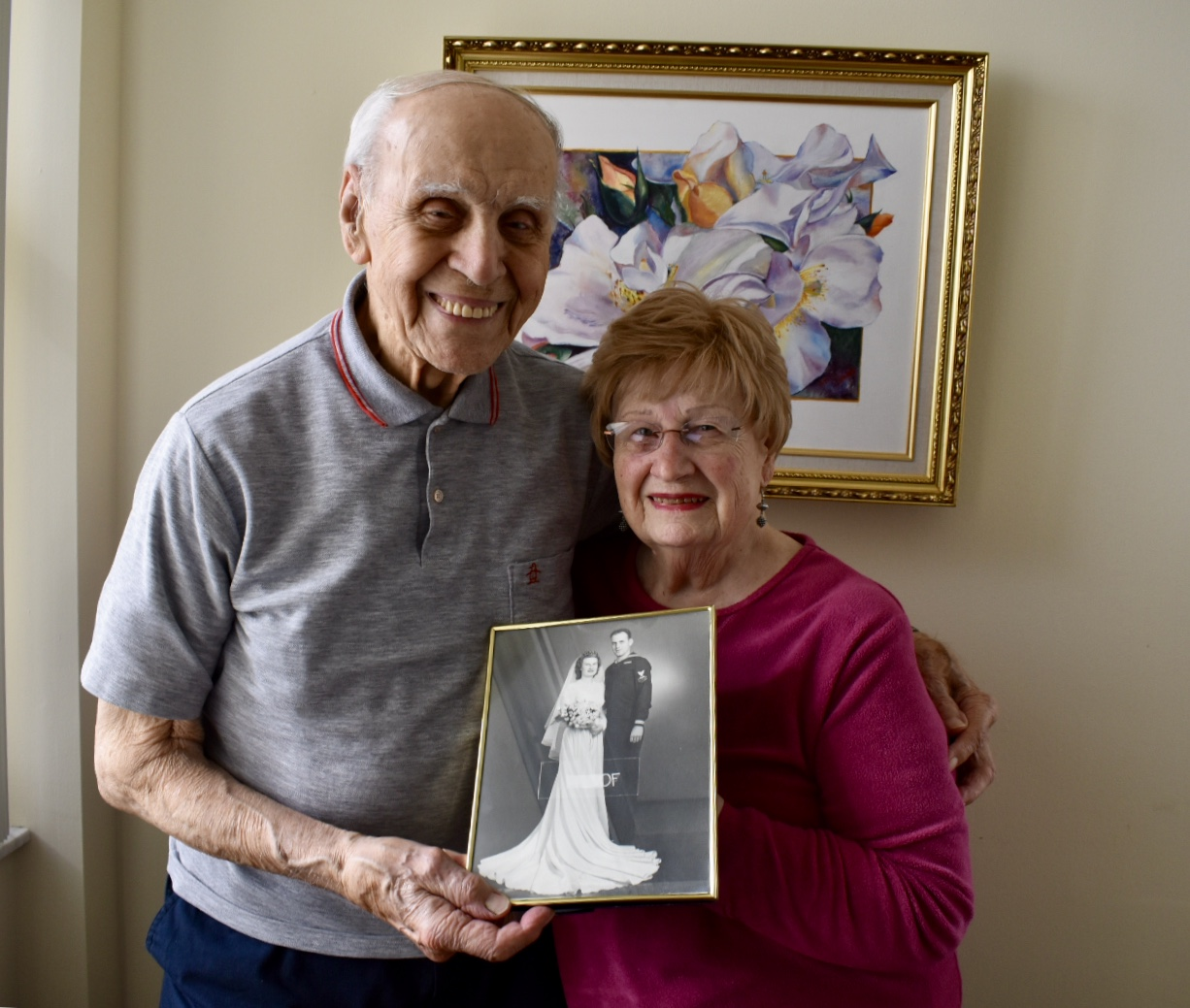 An older man and woman holding a black and white photo of their wedding day, standing in front of a flower painting.