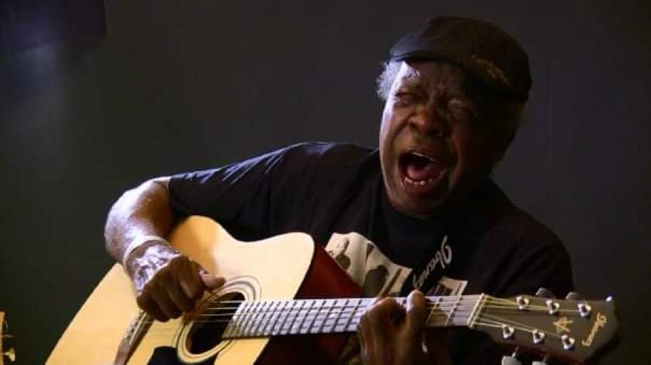 A man plays guitar and sings, wearing black shirt and black ball cap.
