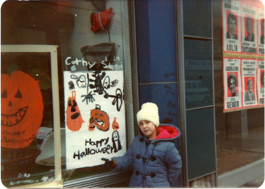 A girl in a blue coat and white cap stands next to a window decorated with children's Halloween art.