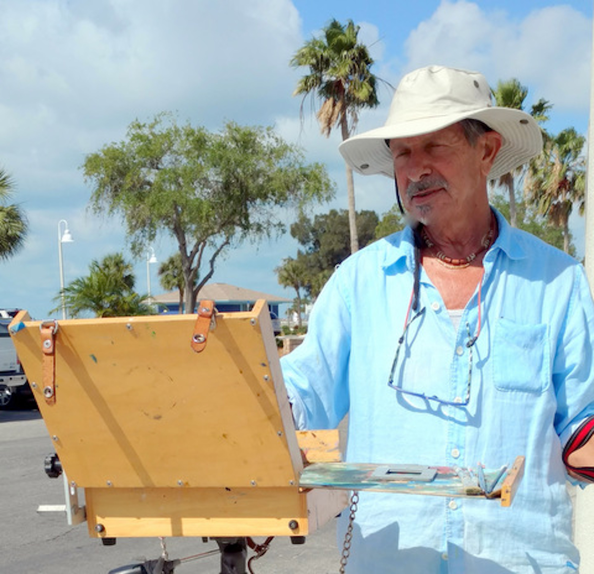 A man in a blue shirt and white hat painting outside.