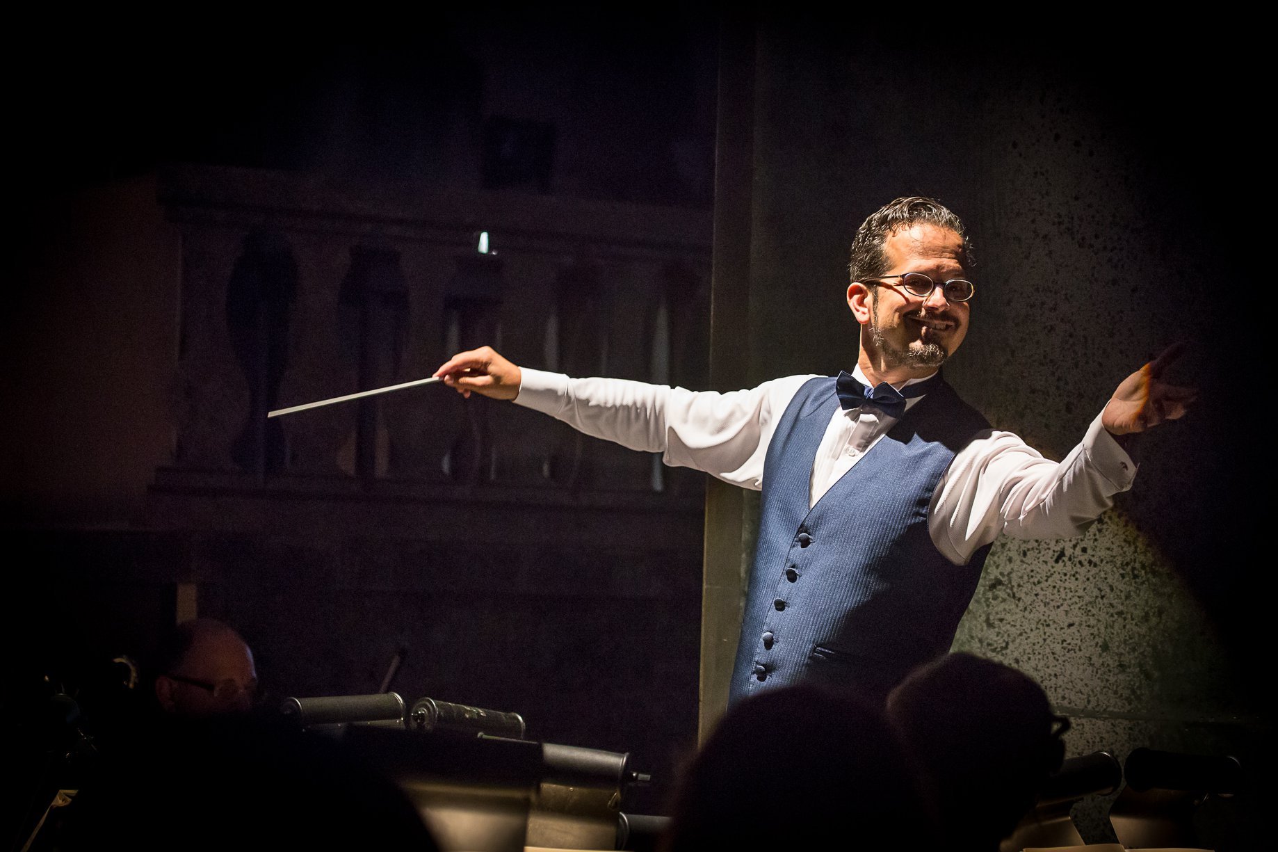 A conductor with a baton and arms outstretched, wearing a blue vest and bow tie, smiles to the camera.