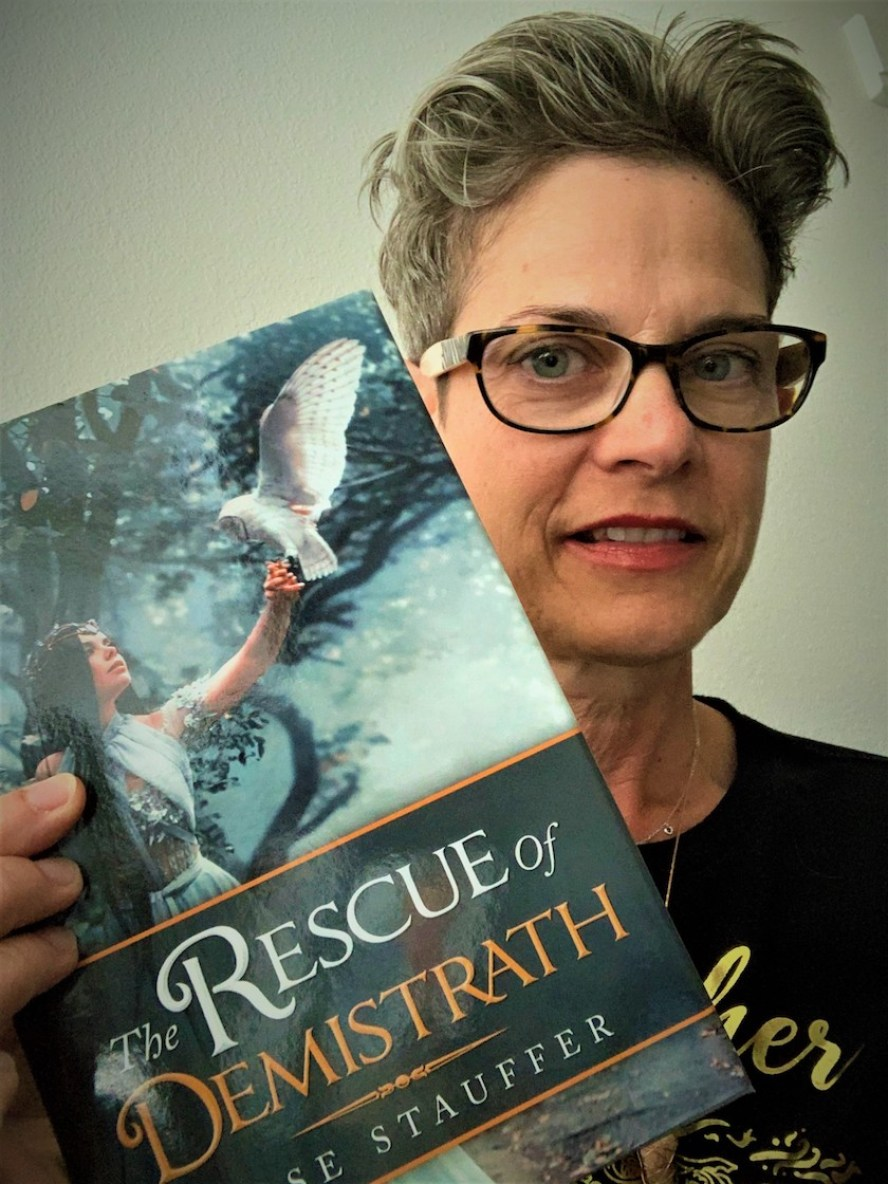 "A woman with glasses holding up a book with the title""The Rescue of Demistrath"""