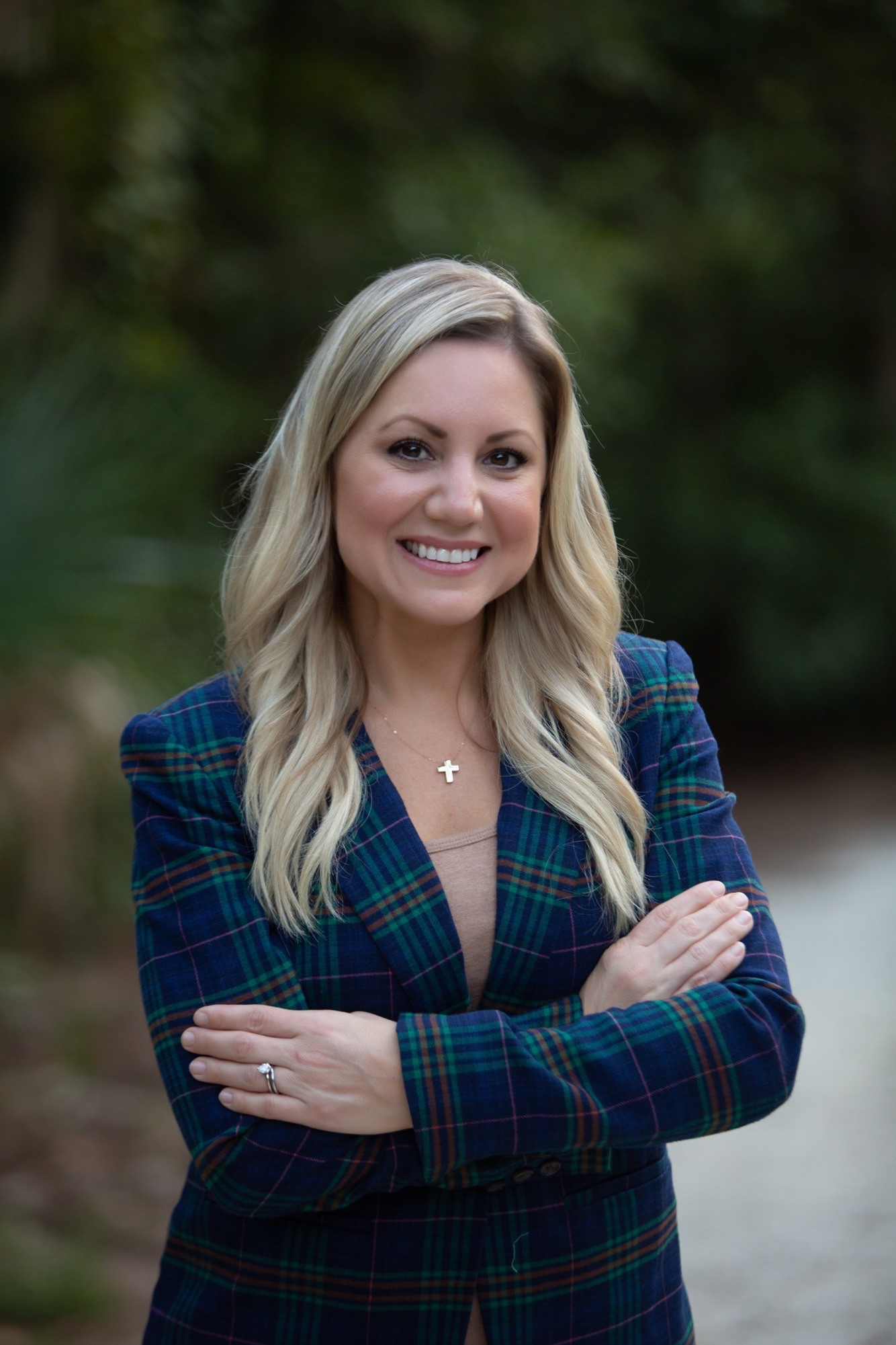 A woman in a blue plaid blazer and cross necklace with arms crossed, smiling at camera.