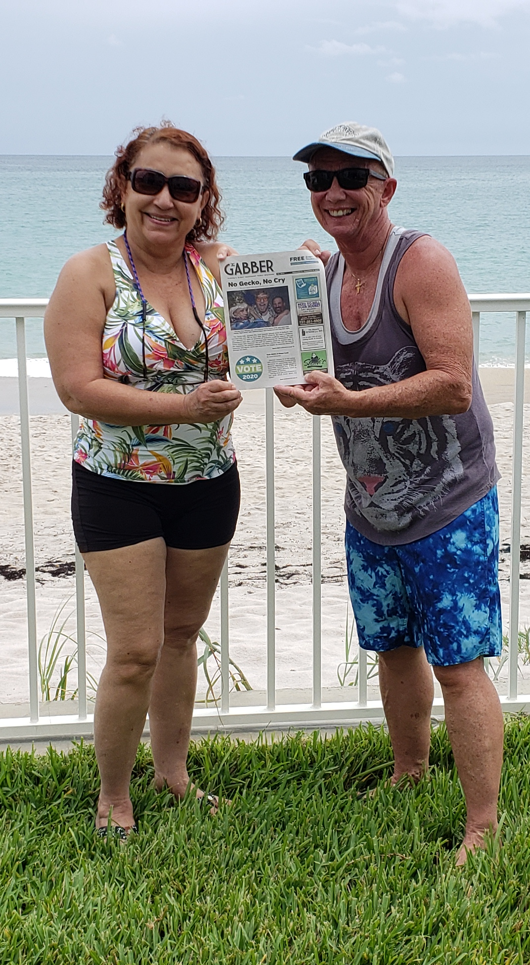 Two people on a beach in front of a fence holding a Gabber Newspaper