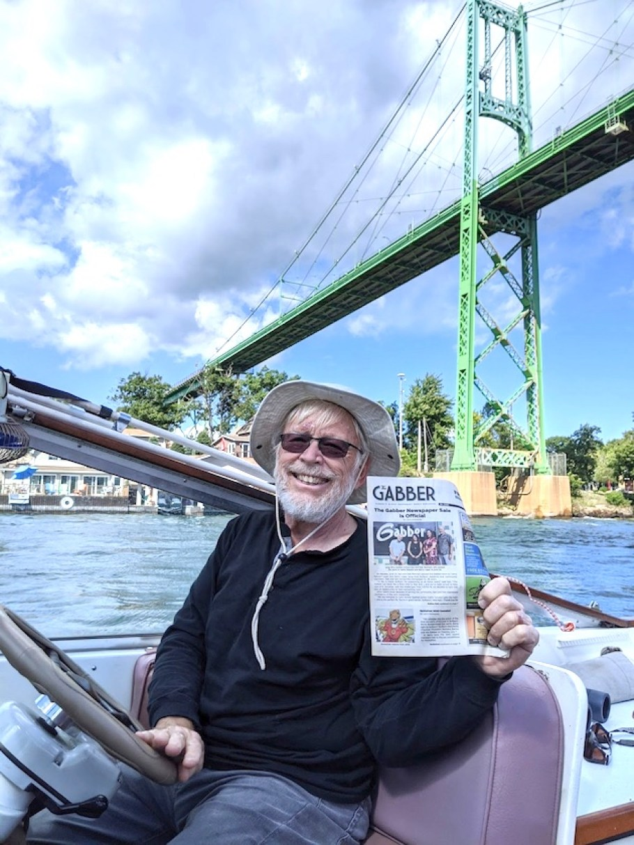 A man in a boat under a large green bridge holding a copy of the Gabber Newspaper.
