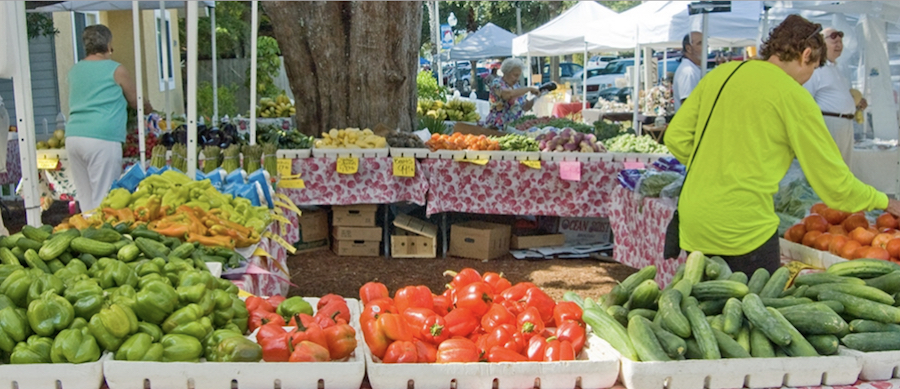 A photo of outdoor produce stands with a shopper in a green shirt.