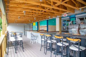 chairs sitting empty bar under wooden ceiling