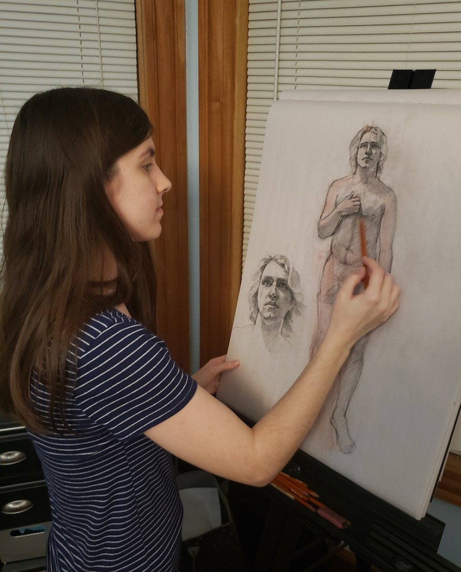 A woman drawing a figures of a man.