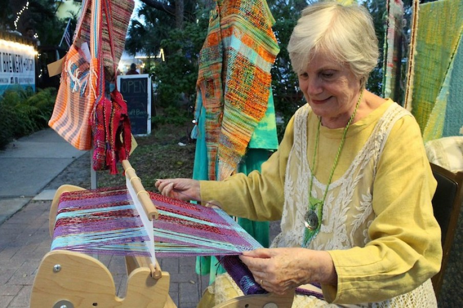 A woman in a yellow dress works at a loom outdoors weaving colorful fabric.