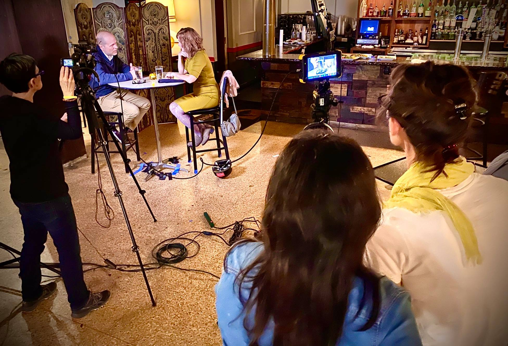 A photo of a film set with two actors seated at a table and a person behind a camera.