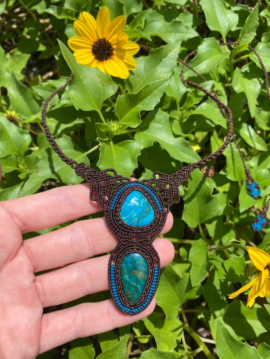 A large dark metal and turquoise necklace in a hand, in front of a green plant with yellow flowers.
