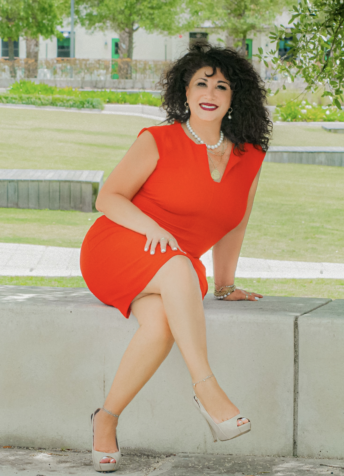 A woman with dark hair and a red dress sits with legs crossed outside looking at the camera.