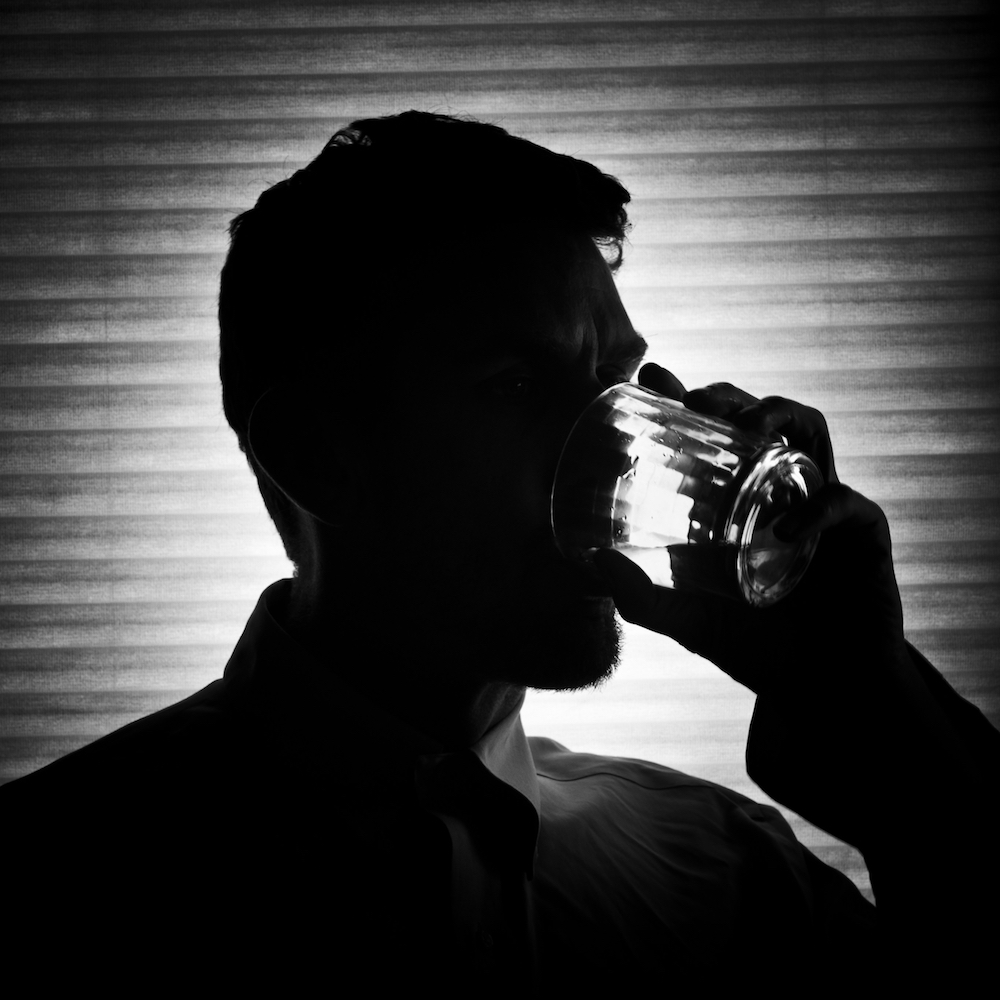 A silhouette of a man drinking