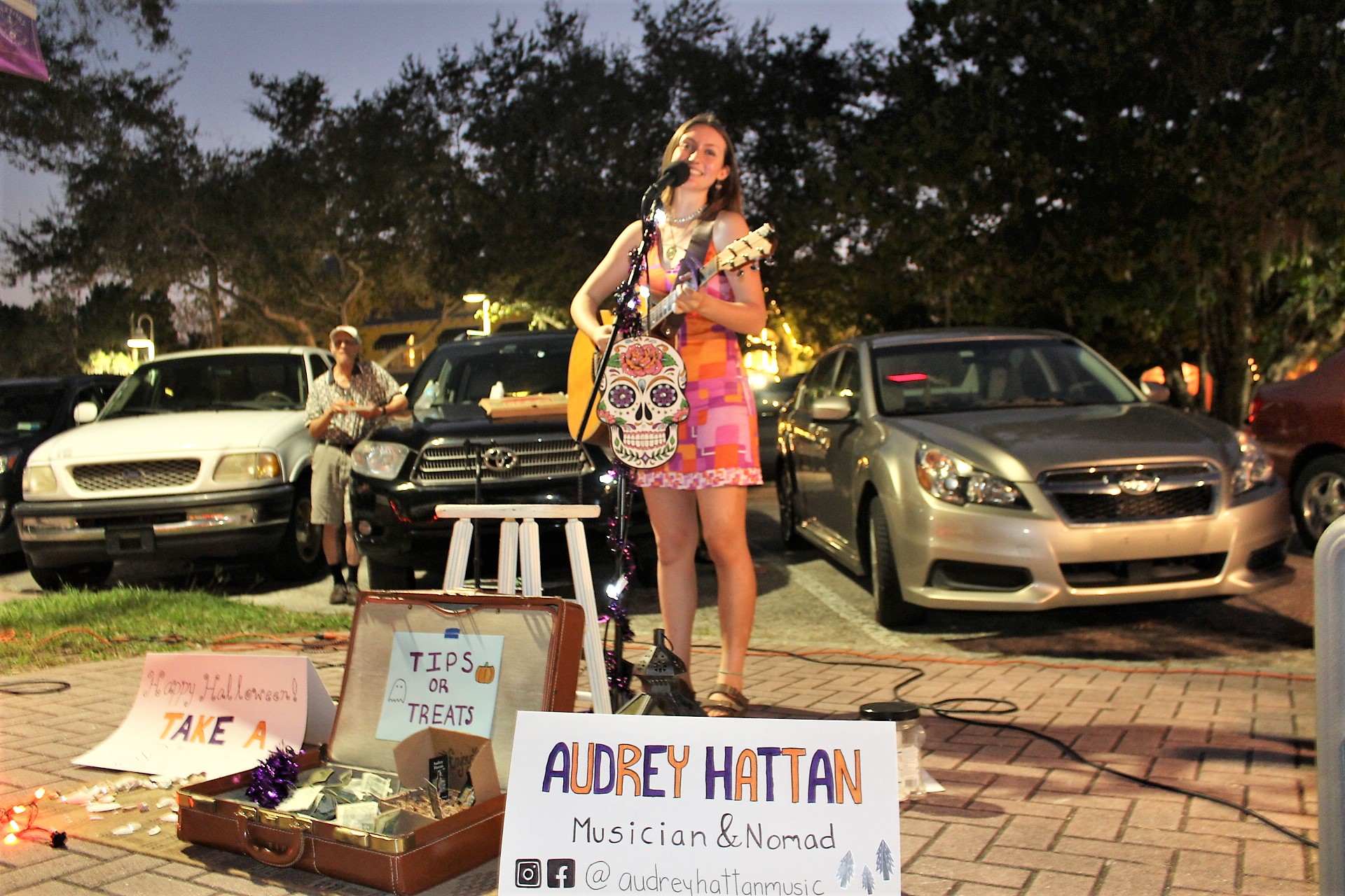 """A young woman stands outside at night playing guitar, in front of a sign that reads """"Audrey Hattan"""""""