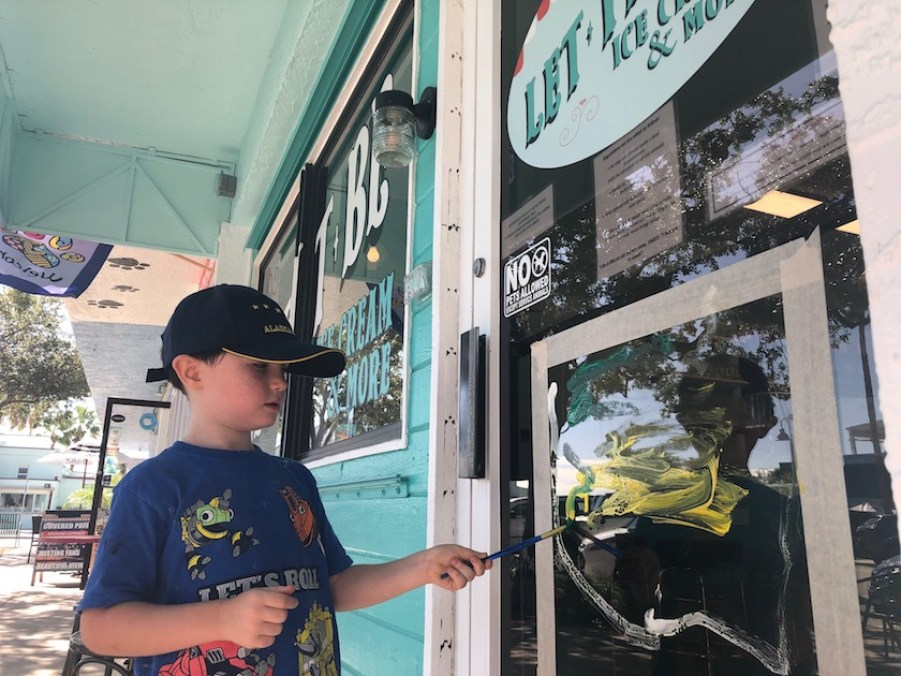 A little boy in a blue shirt and blue ball cap painting a scene on a glass shop door.