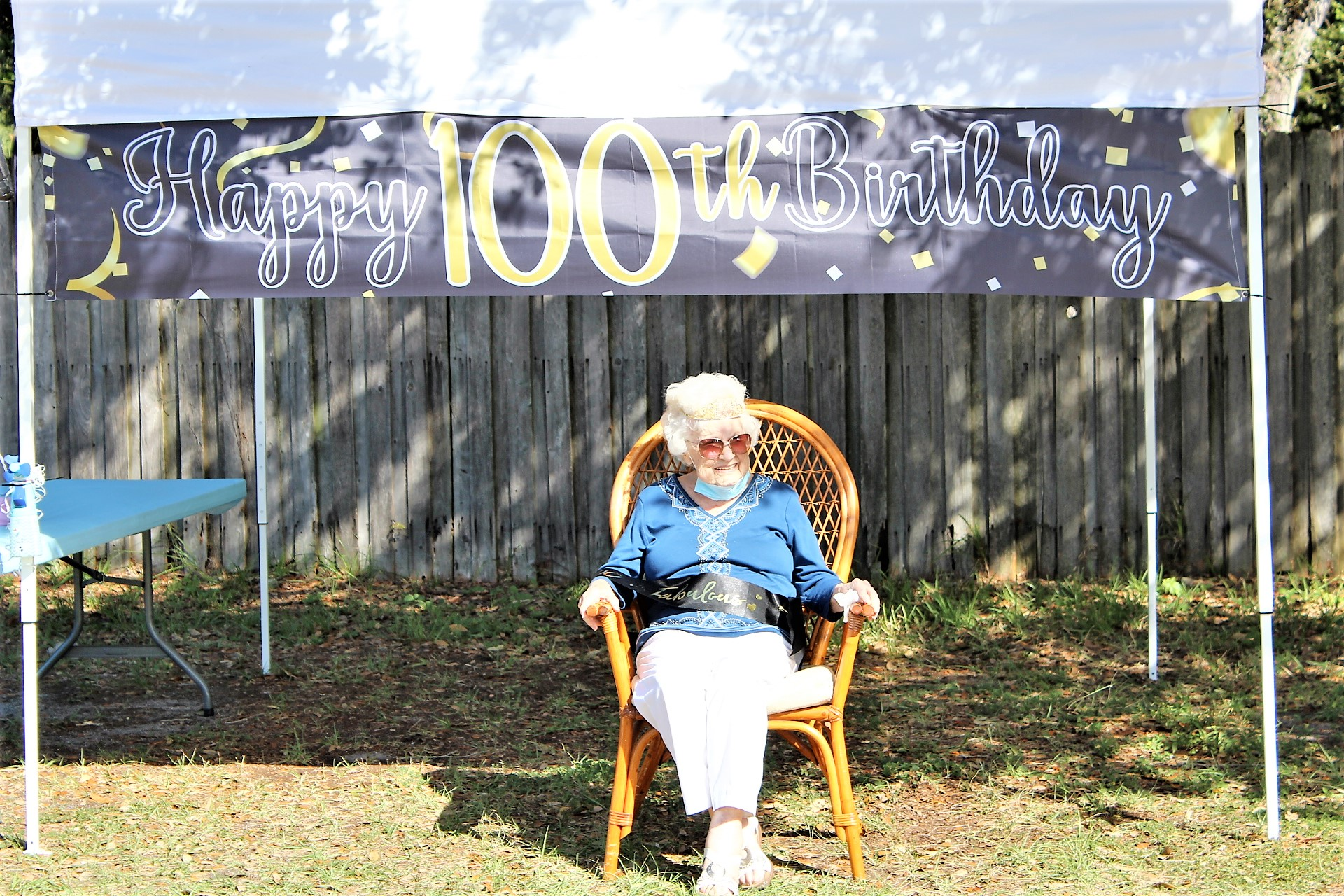 "An elderly woman sits in a chair outside under a banner that reads ""Happy 100th Birthday!"""
