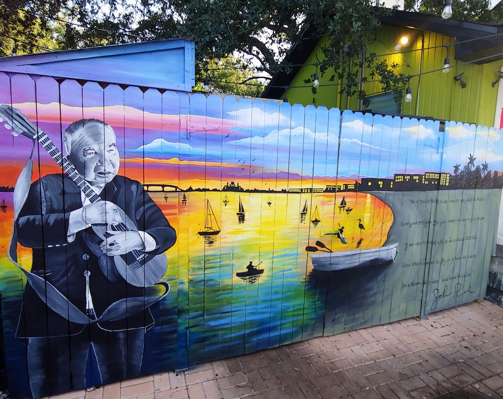 A colorful mural depicting a beach scene with a portrait of John Prine with a guitar.