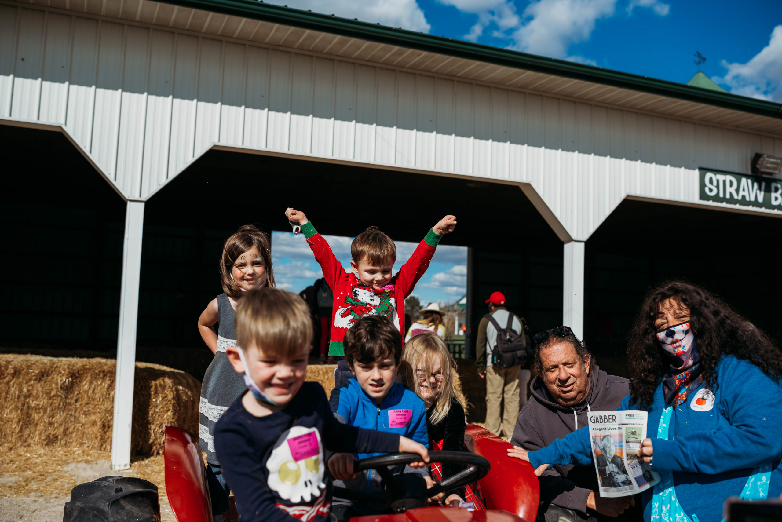 A family group shot of children and adults at a pumpkin patch with a Gabber newspaper
