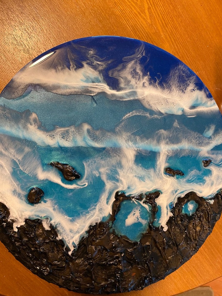 A circular medallion with waves and ocean scene on it.