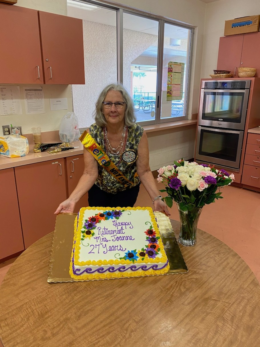 "A woman in a kitchen poses in front of a large cake that reads ""Happy Retirement Mrs. Joanne, 27 Years."""