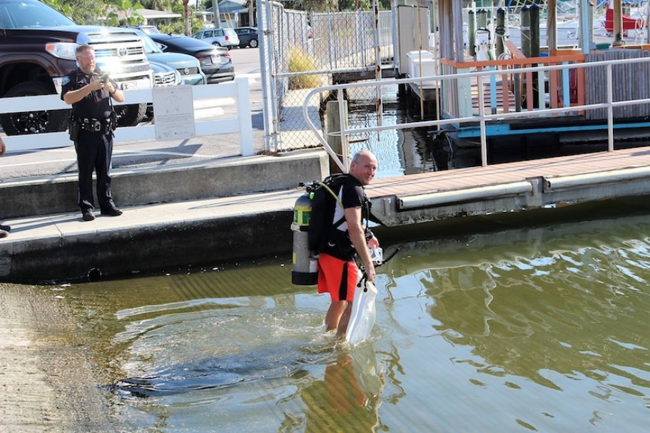 A man in diving gear and bright orange shorts wades into the water at a marina boat ramp.