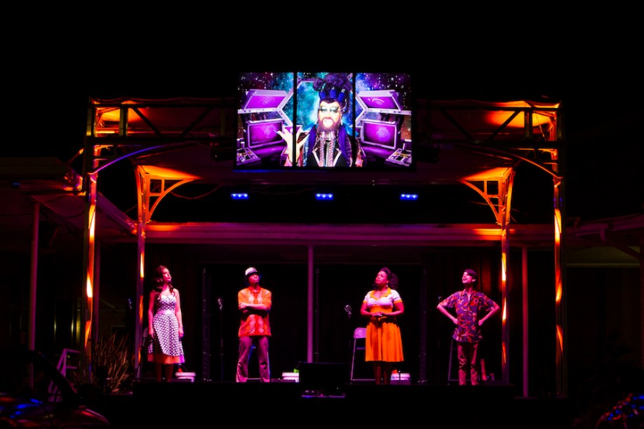 A nighttime stage setup with four performers and a large screen above them featuring an alien character