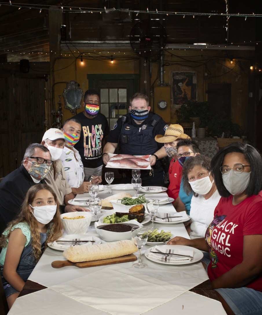 A scene of people sitting around a white table wearing face masks.