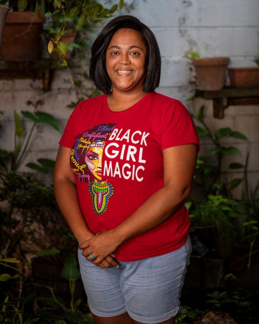 """A woman in a red shirt that says """"Black Girl Magic."""""""
