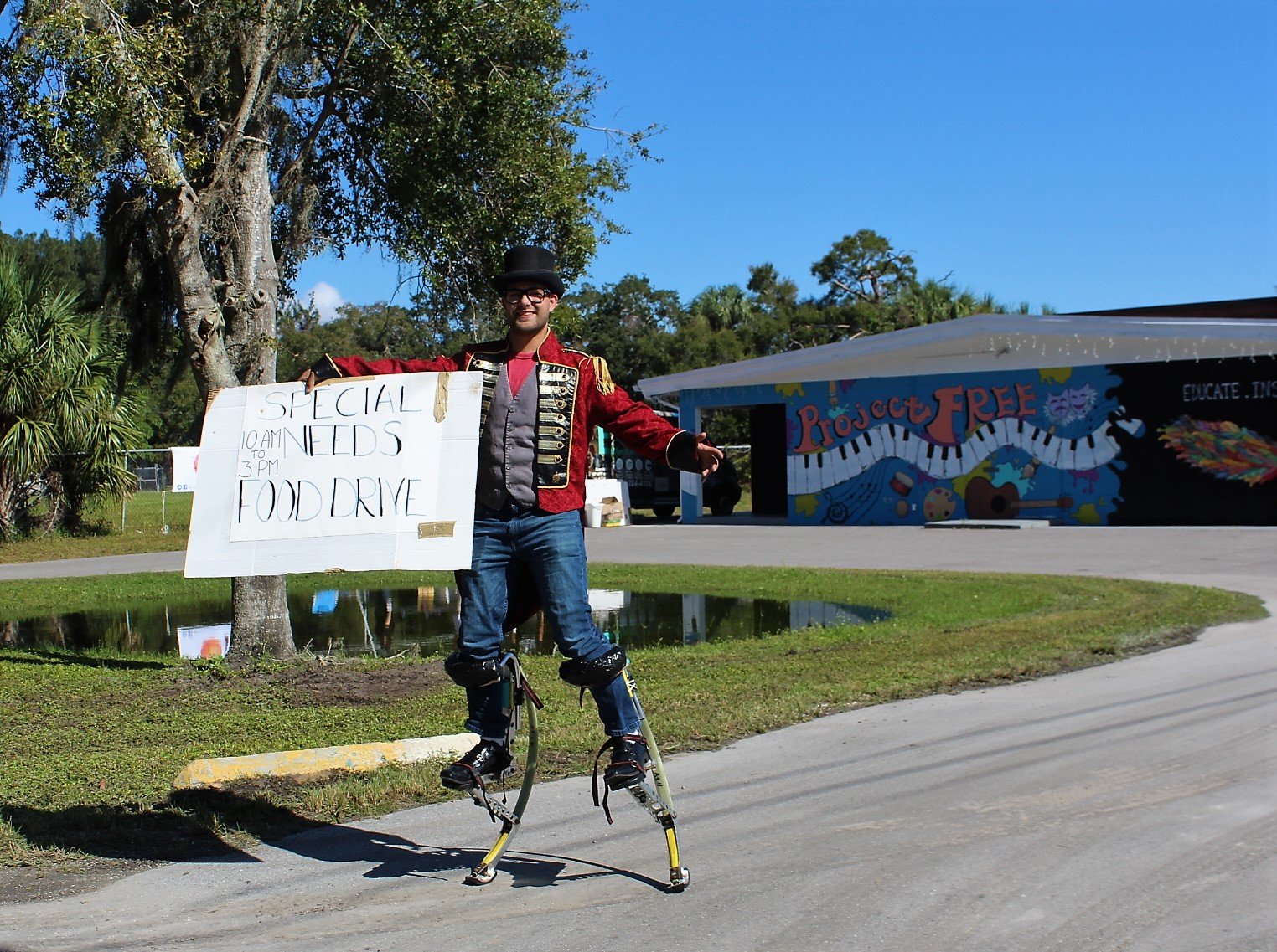 A man on stilts carrying a white sign.