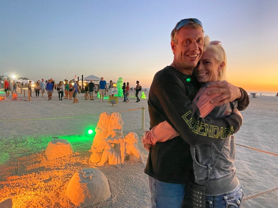 A mand and a woman hugging in front of a sand sculpture on the beach