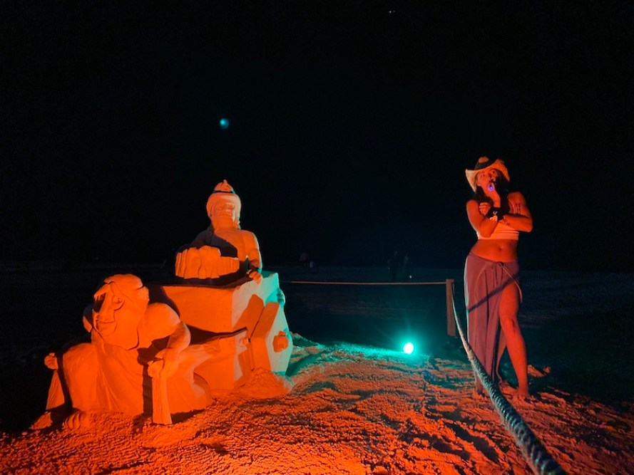 A woman next to a sand sculpture at night.