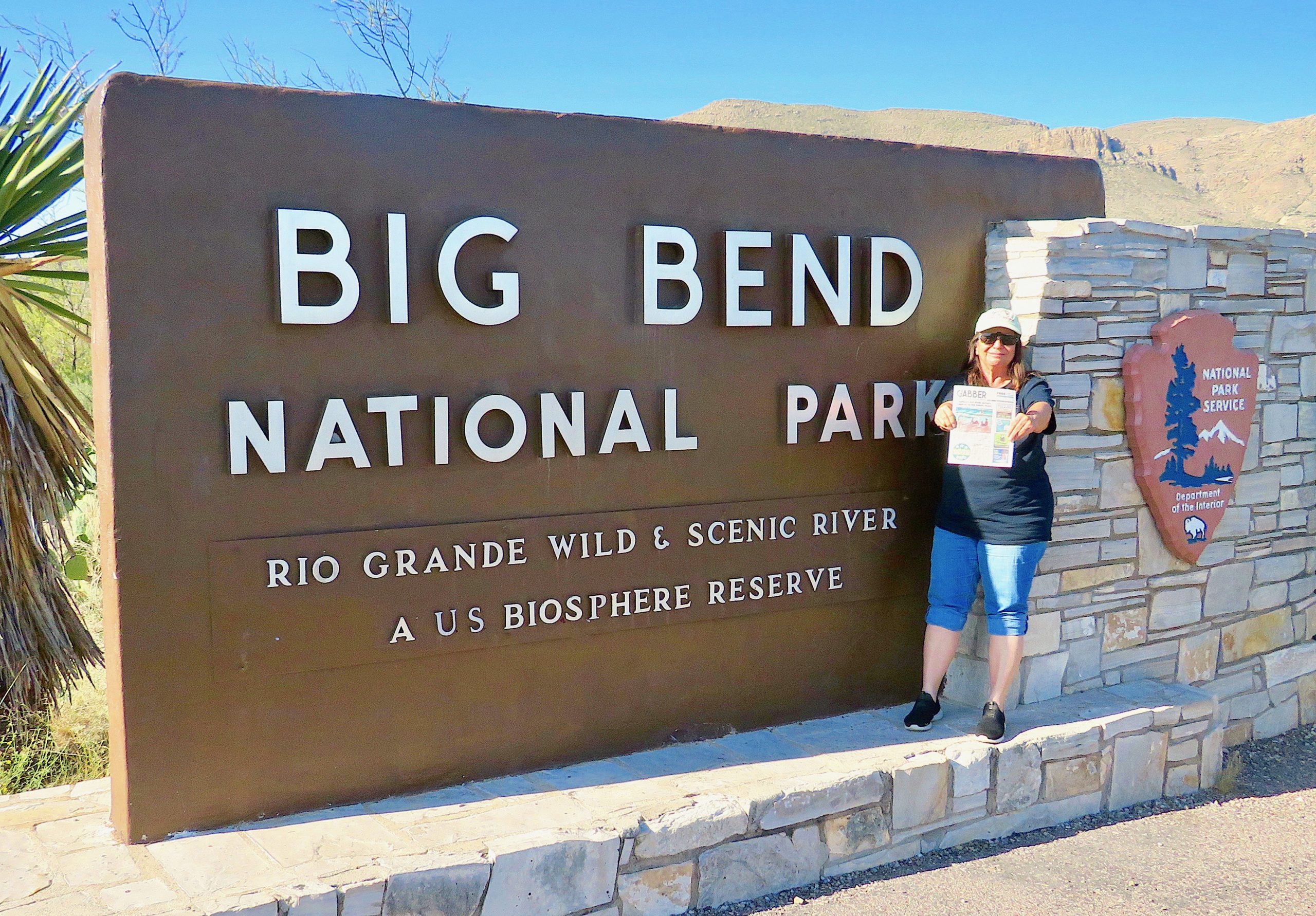 "A woman stands in front of a large sign that reads ""Big Bend National Park"""