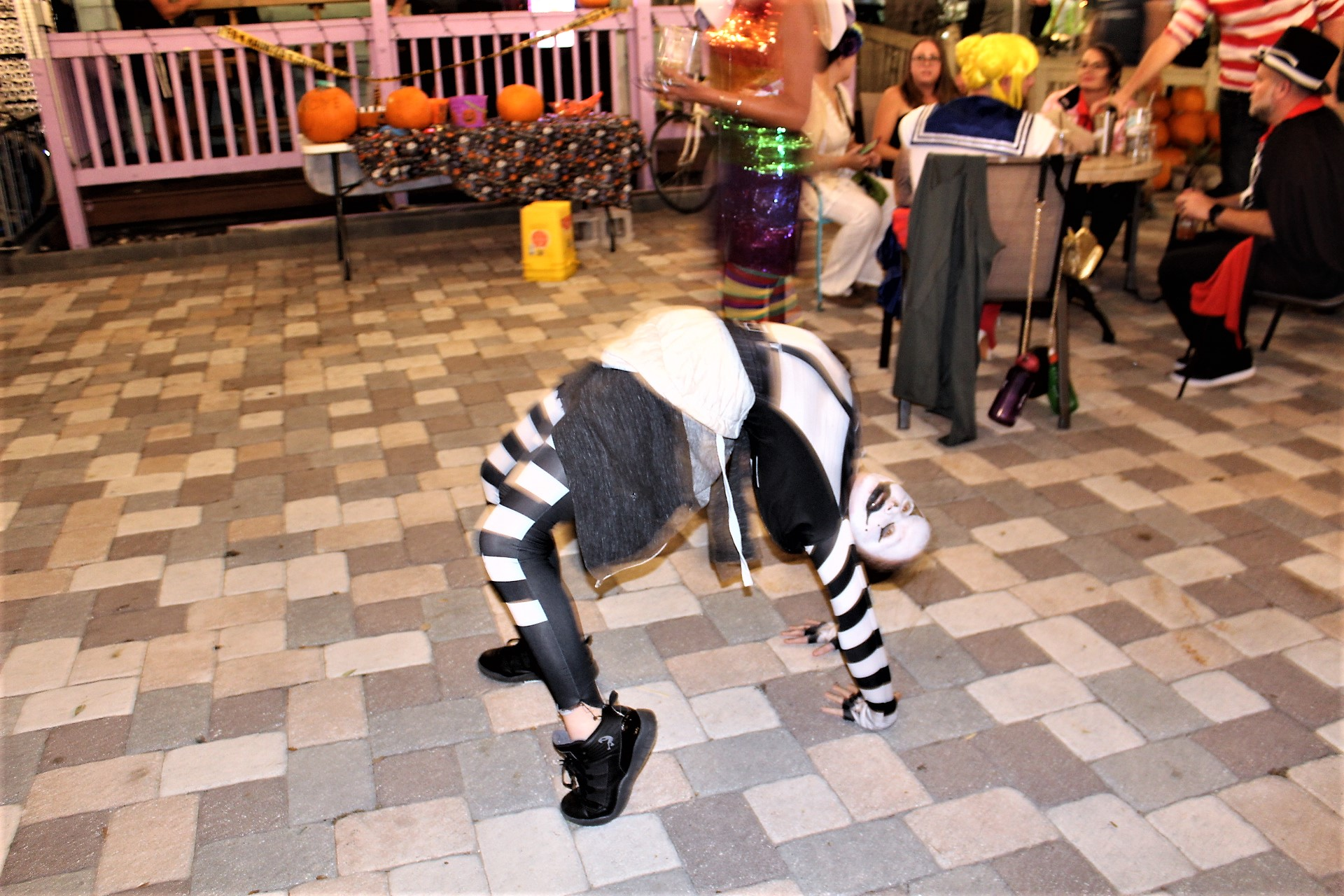A person in black and white costume bent over backwards in a courtyard.