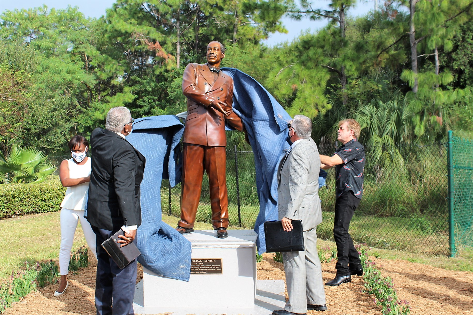 A group of four people unveil a bronze statue of a man outside