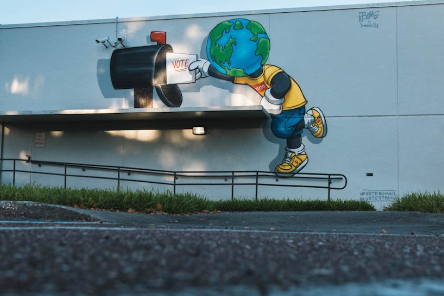 A mural on the side of a building with a character with a globe head putting a ballot in a mailbox.